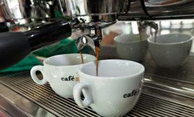 Zwei Tassen Kaffee unter einer Kaffeemaschine